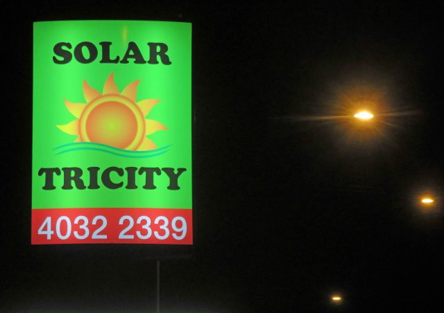 Street sign on a main road in Cairns Australia advertising solar energy. The light which enables this sign to work at night is provided by coal. Photo: David Clode.